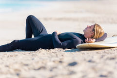 I need some rest. A young surfer with his board on the beach Stock Images