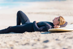 I need some rest. A young surfer with his board on the beach Stock Image