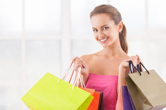 I need some retail therapy. Attractive young woman holding shopping bags and smiling at camera Stock Images