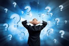 I need to find the answer!. Rear view of businessman with arms on head thinking something over Royalty Free Stock Photo