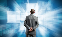 I need to find the answer!. Rear view of businessman with arms on head thinking something over Royalty Free Stock Image