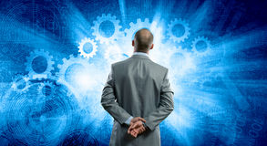 I need to find the answer!. Rear view of businessman with arms on head thinking something over Royalty Free Stock Photos