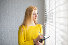 I need to think and write it down. A photo of young woman thinking about something to write it down. She's looking outside the window royalty free stock photos