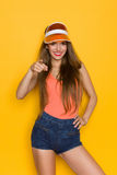 I Need You. Smiling young woman in orange shirt and sun visor pointing at camera. Three quarter length studio shot on yellow background Stock Photos