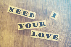 I Need Your Love message. Written with wooden blocks on a wooden table. Image cross processed for grunge look Royalty Free Stock Image