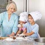 I nipoti aiutano la nonna a cuocere al Natale immagini stock