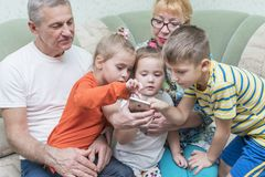 I nonni con i nipoti esaminano lo smartphone immagine stock libera da diritti