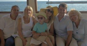 I nonni felici del padre della madre del bambino della famiglia stanno sedendo sulla piattaforma chiusa della barca stock footage