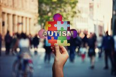 Symbol of Autism as a child hand holding a colorful puzzle piece over a crowded street background stock photos