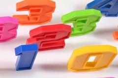 I numeri di plastica variopinti si chiudono su su un bianco Immagine Stock Libera da Diritti