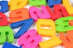 I numeri di plastica variopinti si chiudono su su un bianco Immagine Stock