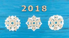 I numeri 2018 e tre fiocchi di neve di legno sulla vecchia tavola di legno blu Immagini Stock Libere da Diritti