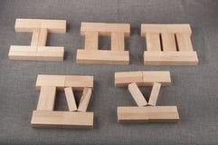 I numeri romani di legno fatti dei mattoni del giocattolo mettono sul fondo grigio del tessuto Immagini Stock Libere da Diritti