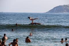 I nuotatori del bagnante possono affittare i bordi di per stare sulla pagaia alla spiaggia di Ipanema Fotografie Stock