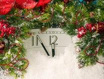 I nuovi anni cronometrano ed i rami dell'abete coperti di neve Fotografia Stock
