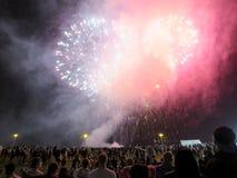 I nuovi anni di fuochi d'artificio interrompono l'aria come esposizione dell'orologio della gente a Fotografie Stock Libere da Diritti