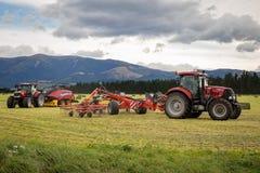 I nuovi trattori rossi dell'Olanda funzionano la falciatura, il rastrellamento ed il fieno pressato immagini stock