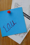 I.O.U and receipts. Blue note with IOU written in felt pen thumb tacked to a wooden notice board with till receipts Royalty Free Stock Image