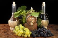 I oakcasks med svarta vines och druvor som är vita och Royaltyfri Bild