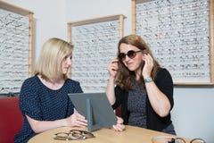 I optiker shoppa kvinnan som väljer ny solglasögon Arkivbild