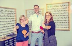 I optiker shoppa kvinnor och mannen med tummen upp och handspegel s Royaltyfri Foto