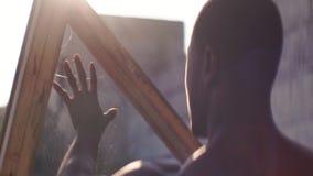 I outdors diritti dell'uomo di colore sulla vecchia fabbrica, esaminando la sua mano, toccante il web, lo strappa, lense anamorfi stock footage