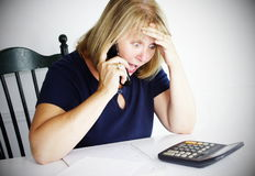 I Owe How Much?!. Older blonde woman is shocked by her debt. She is on the phone looking over her calculator Royalty Free Stock Photography