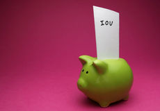 I owe You. A green piggy bank on pink background, shot slightly from the side with an IOU note in it Royalty Free Stock Images