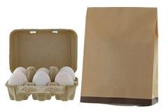 I pacchetti del vassoio dell'uovo della cartapesta delle uova fresche accanto a marrone riciclano Immagine Stock