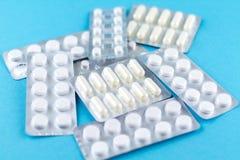 I pacchetti delle capsule e delle pillole bianche hanno imballato in bolle con lo spazio della copia su fondo blu Fuoco su priori Immagine Stock