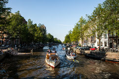 I PAESI BASSI, AMSTERDAM - 22 AGOSTO 2015: Veiw sul ponte attraverso il canale del fiume con la barca, immagine tipica dei canali Fotografia Stock
