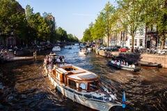 I PAESI BASSI, AMSTERDAM - 22 AGOSTO 2015: Veiw sul ponte attraverso il canale del fiume con la barca, immagine tipica dei canali Immagini Stock
