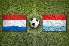 I Paesi Bassi contro Bandiere del Lussemburgo sul campo di calcio Fotografia Stock