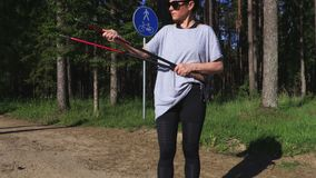 I pali di camminata del nordico della riparazione della viandante della donna vicino trascinano