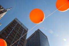I palloni arancio splende in un giorno soleggiato del cielo blu Immagini Stock Libere da Diritti