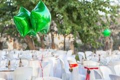 I palloni brillanti verdi al giardino presentano la regolazione per il recepti di nozze Immagine Stock