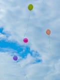 I palloni multicolori volano contro il cielo blu e le nuvole Fotografia Stock