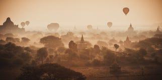 I palloni sorvolano migliaia di tempie nell'alba in Bagan, Myanmar Immagini Stock