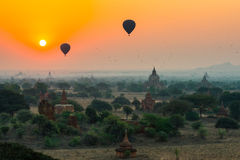 I palloni sorvolano migliaia di tempie nell'alba in Bagan, Myanmar Immagine Stock