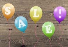 I palloni variopinti luminosi del partito con la vendita del testo sulle plance di legno imbarcano Immagini Stock