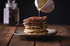 I pancake casalinghi impilano dei pancake con miele su fondo di legno immagine stock libera da diritti