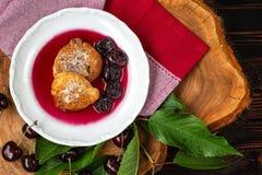 I pancake in ciliegia sauce in un piatto e nelle bacche della ciliegia con le foglie verdi su un bordo di legno fotografia stock