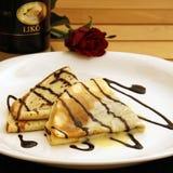 I pancake con la salsa e lo zabaione di cioccolato sono servito su una zolla Fotografia Stock