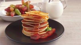 I pancake delle frittelle su un piatto versa il movimento lento dello sciroppo del miele archivi video