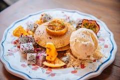 I pancake dolci con miele e gelato alla vaniglia fruttificano con l'orango fotografie stock