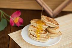 I pancake su un piano d'appoggio sta gocciolando il miele Fotografia Stock Libera da Diritti