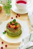 I pancake verdi con spinaci e le banane hanno decorato l'agrume, la menta ed il mirtillo rosso immagine stock