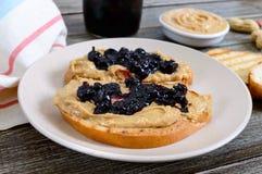 I pani tostati con burro di arachidi e la bacca si inceppano su un piatto su una tavola di legno immagini stock