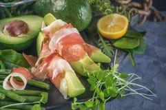 I pani tostati deliziosi dell'avocado e del prosciutto di Parma con verde hanno germogliato la senape ed il limone Copi lo spazio fotografie stock