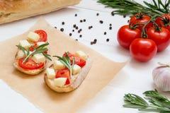 I pani tostati di Bruschetta con la mozzarella, i pomodori ciliegia ed i rosmarini freschi del giardino, si chiudono su immagini stock